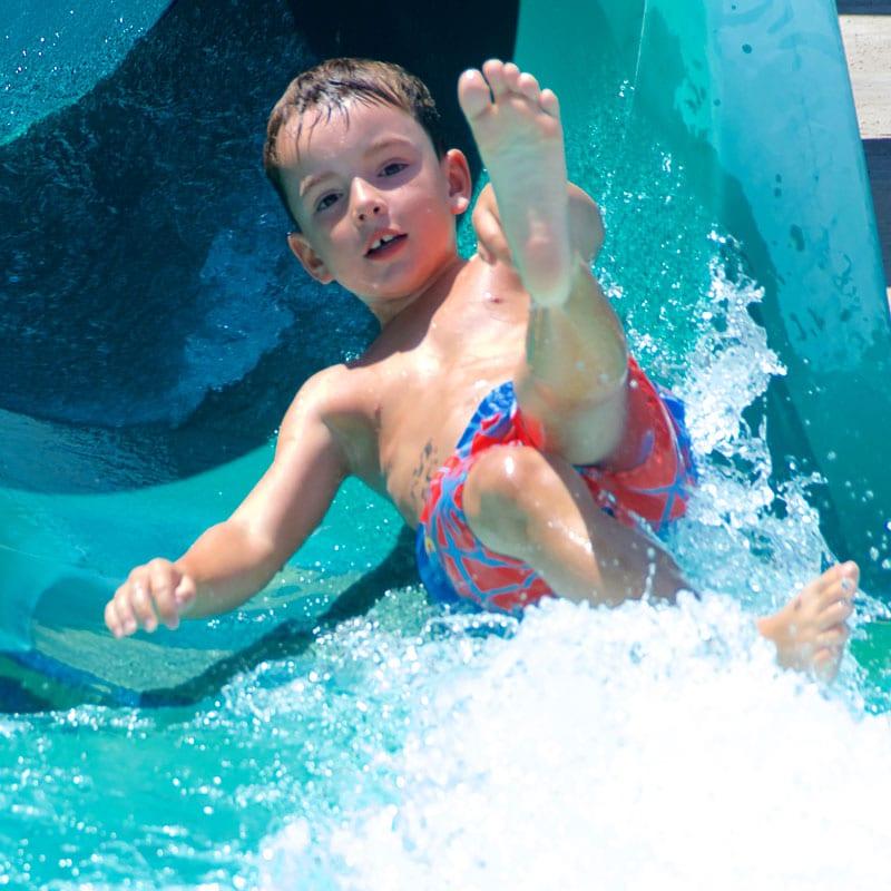 kid rides down waterslide